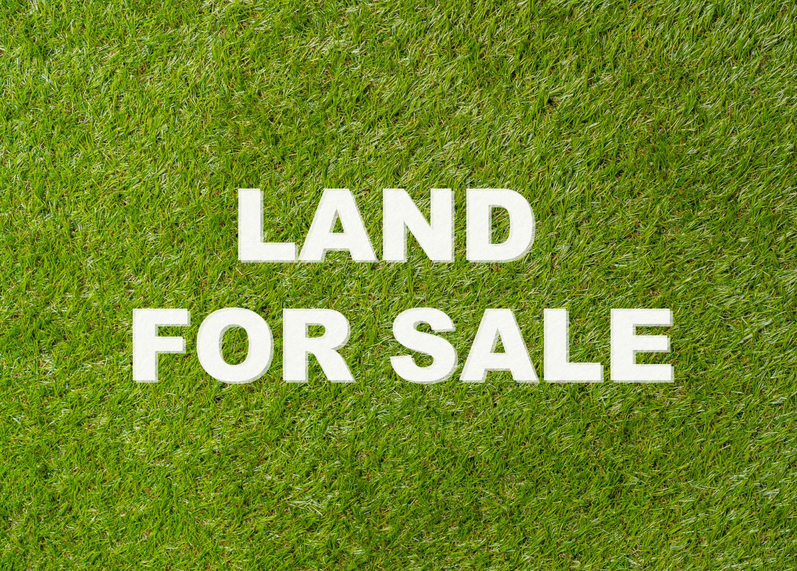 Bare lawn with a land for sale sign, to show land broker services